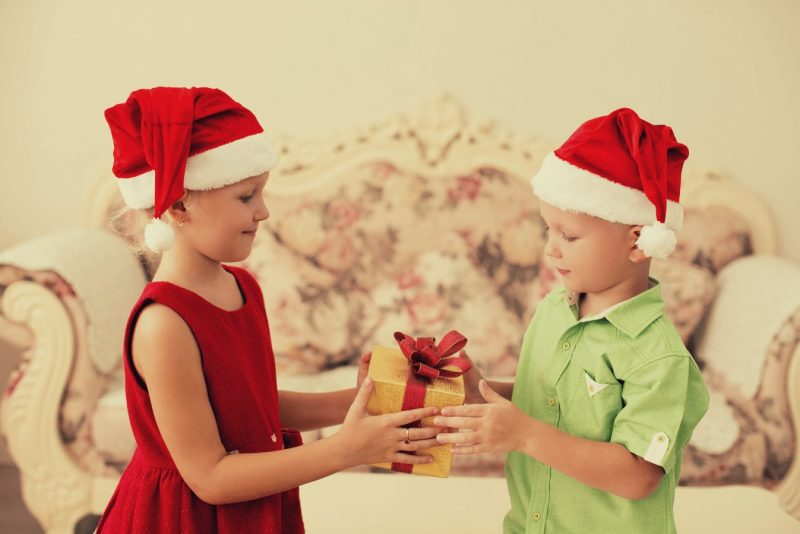 Young Girl Giving Young Boy A Gift