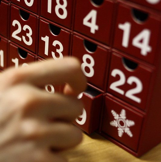 Adult hand opening Cardboard Advent Calendar
