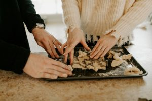 Christmas Cooking Challenge - Two Pairs of hands preparing dough on tray