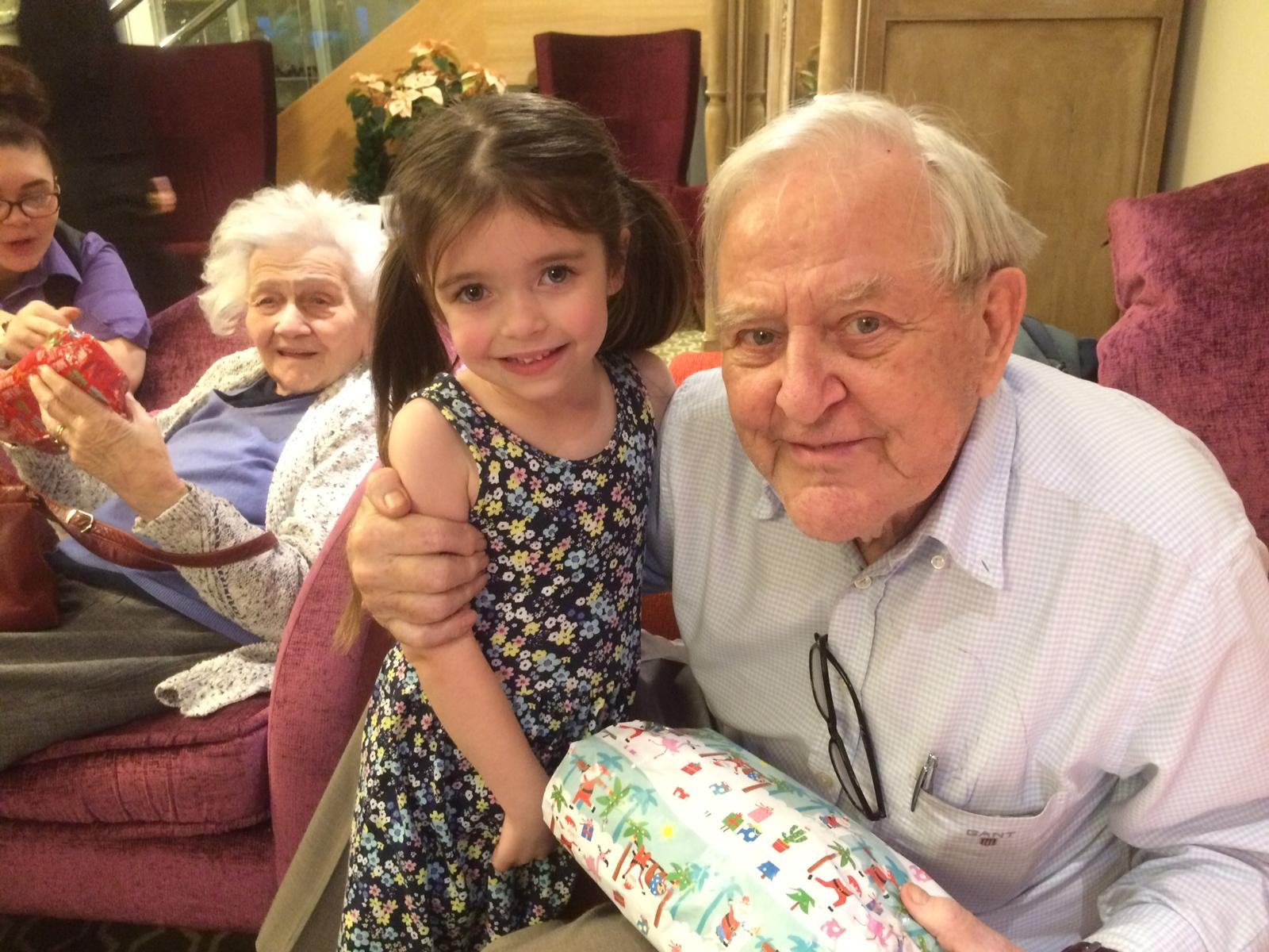 A young member of the Pay It Forward team delivers gift to male resident at Shinfield View Care Home
