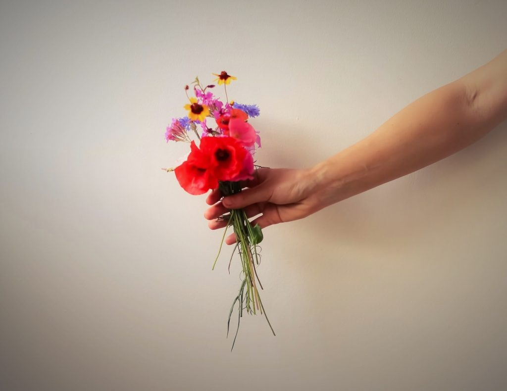 Arm offering flowers