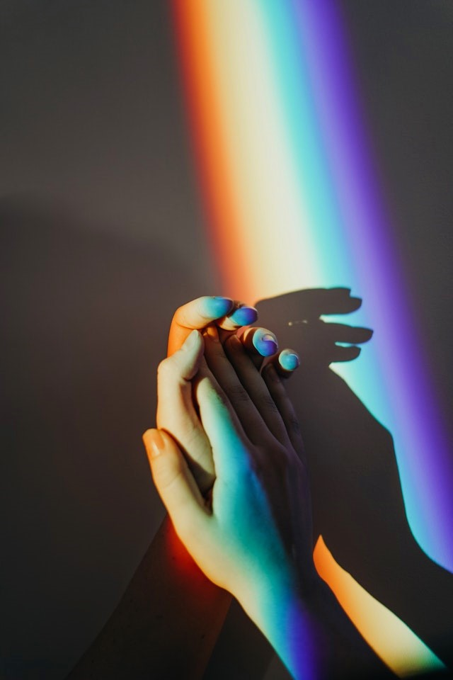 Hands Clapping in Rainbow Light
