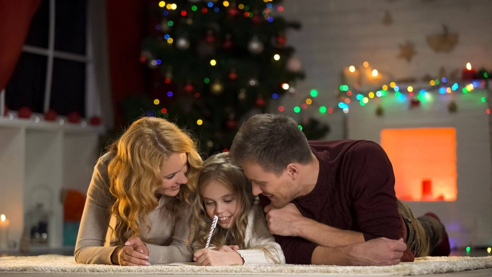Daughter lying on the floor writing Christmas memories with parents either side and Christmas tree in the background