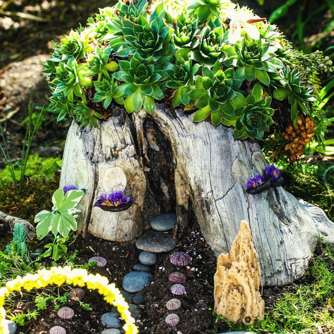 An elf house created from a tree stump with plant roof and coloured stone pathway