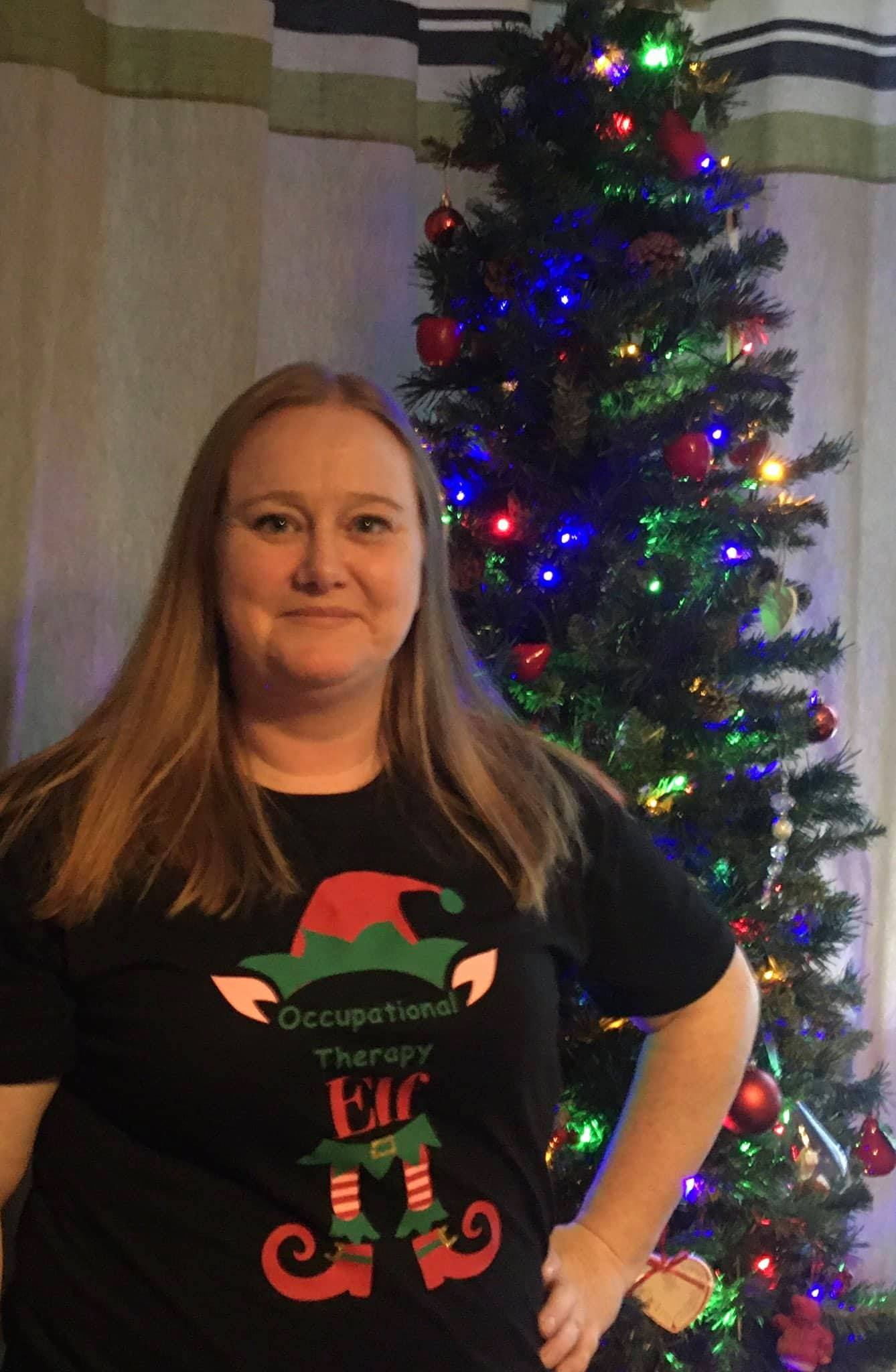 Course Leader with elf t-shirt in front of Christmas tree