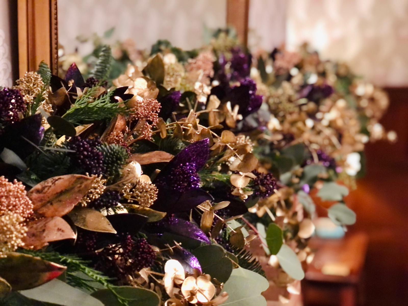 Close-up of fireplace Christmas garland with gold and purple sprayed leaves and decorative extras