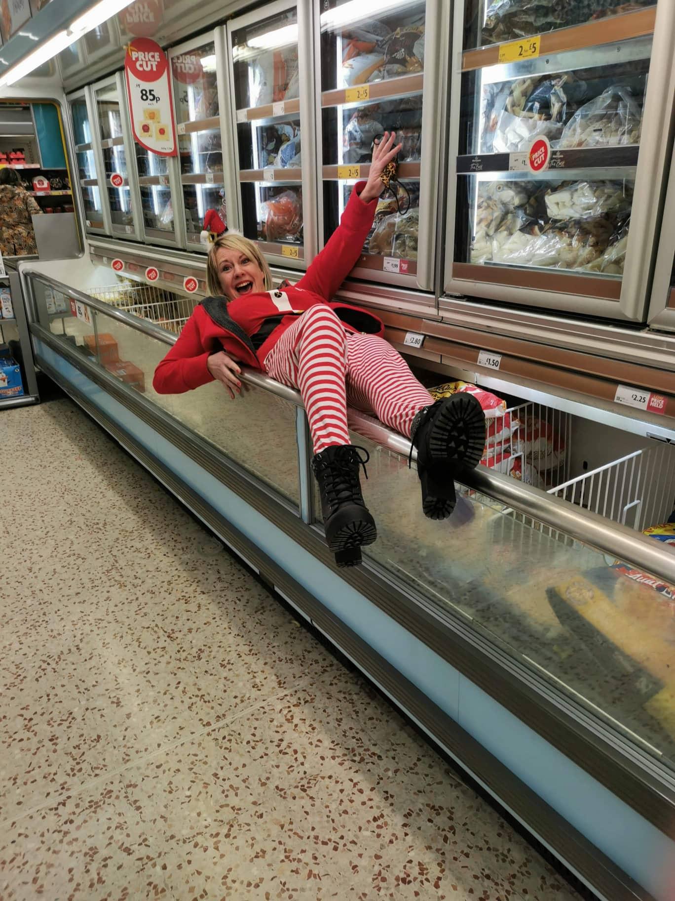 Lady in elf costume lying in supermarket freezer