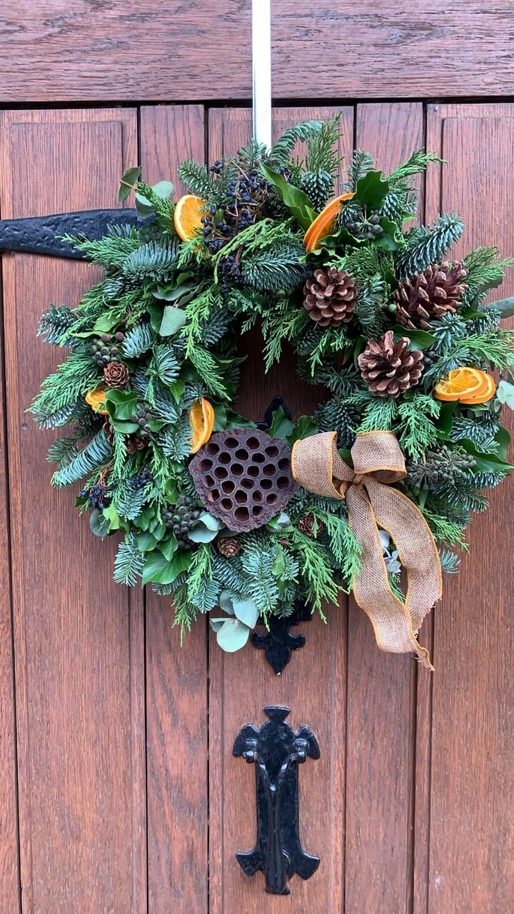 Traditional Style Christmas Wreath with pine cones and orange slices hanging on wooden door