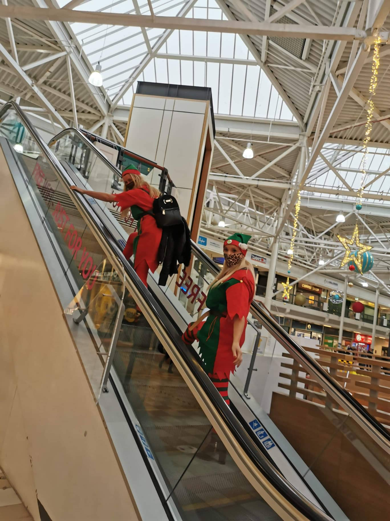 Two women as elves on esculator