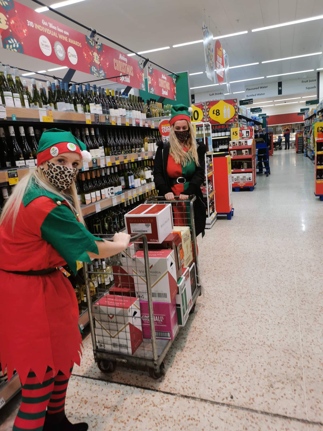 Ladies wearing elf costumes filling trolley with wine bottles