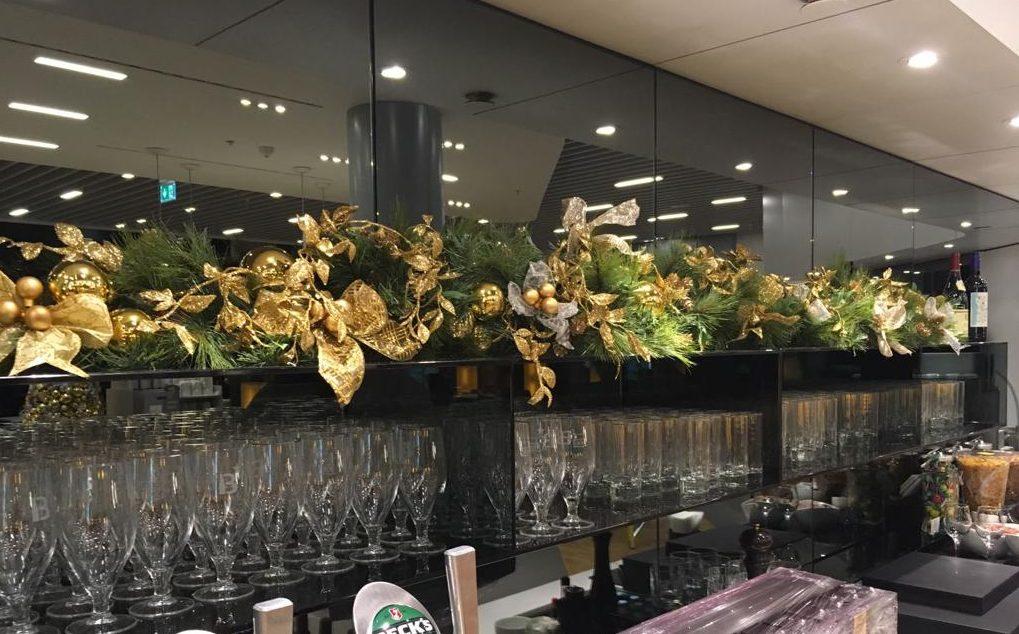 Greenery & Gold Garland along Shelf at back of bar