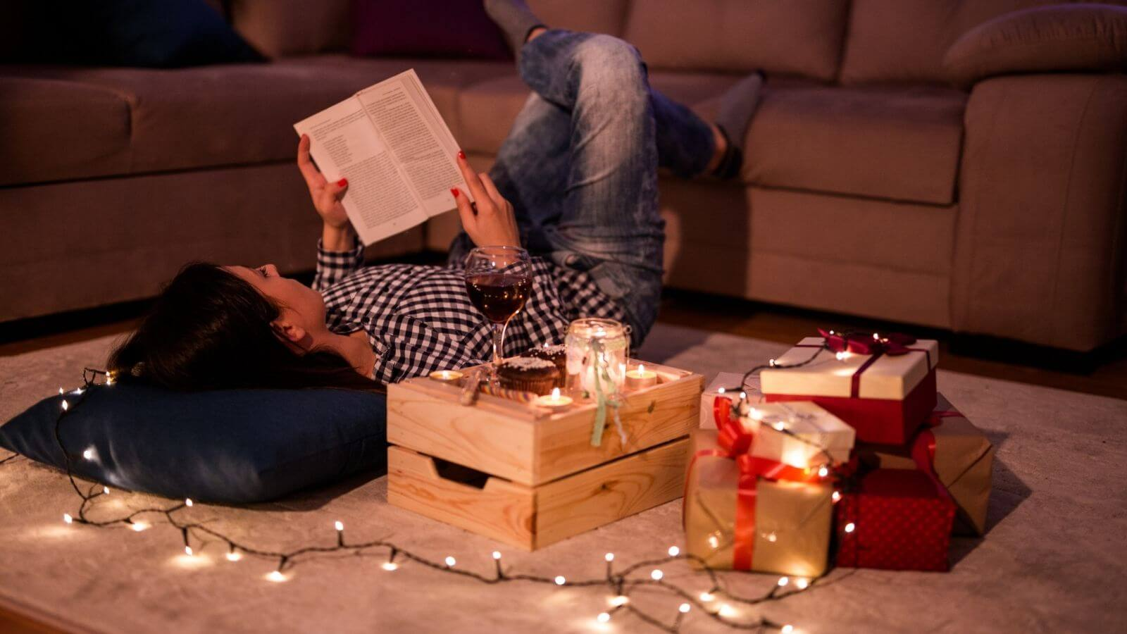 Woman relaxing at Christmas time with book, wine & candles