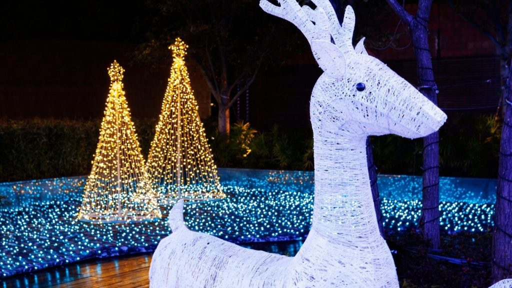 Pair of LED Christmas trees behind an LED reindeer in a garden