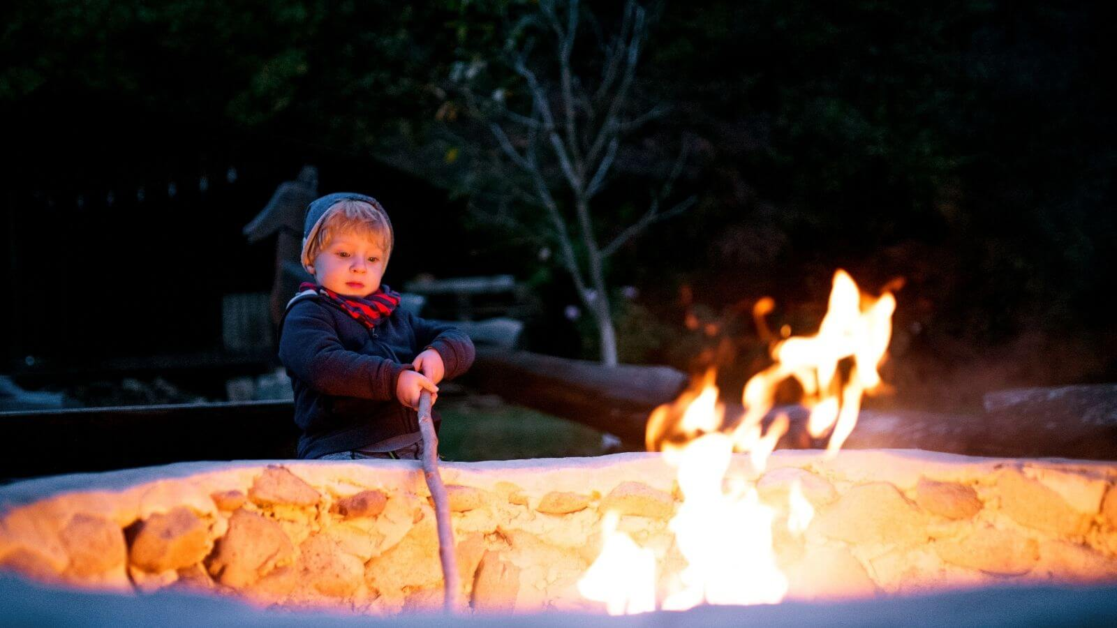 Young boy prodding firepit with a stick