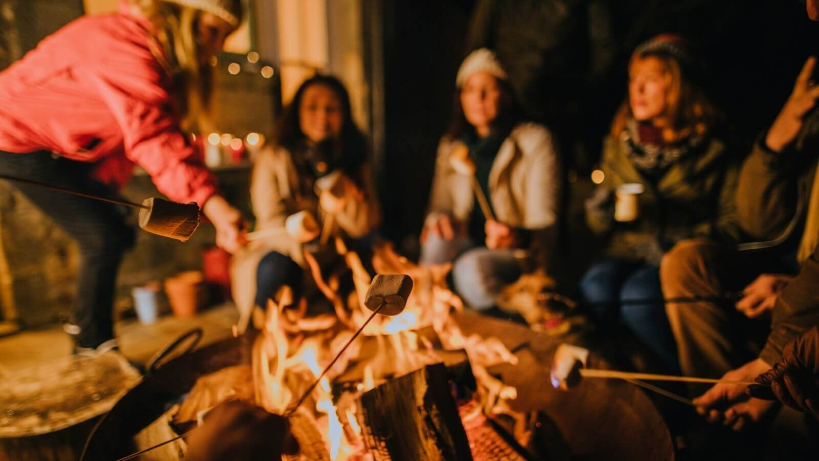 Group of people toasting marshmallows around a firepit