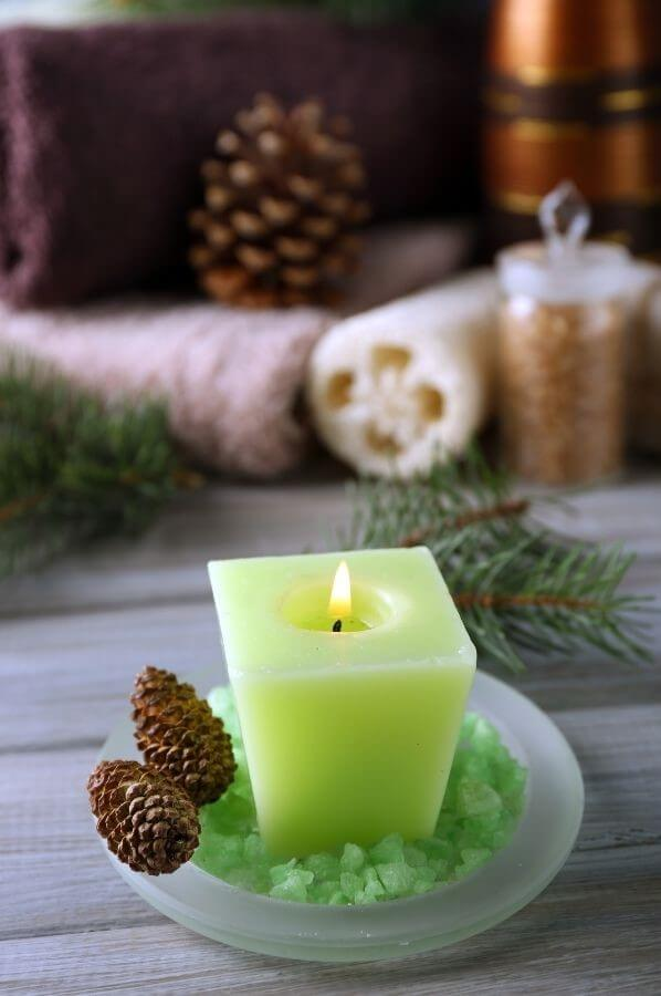 Lime green candle in dish with loafer and towels out of focus in background