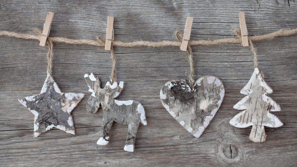 4 rustic wooden ornaments hanging from twine