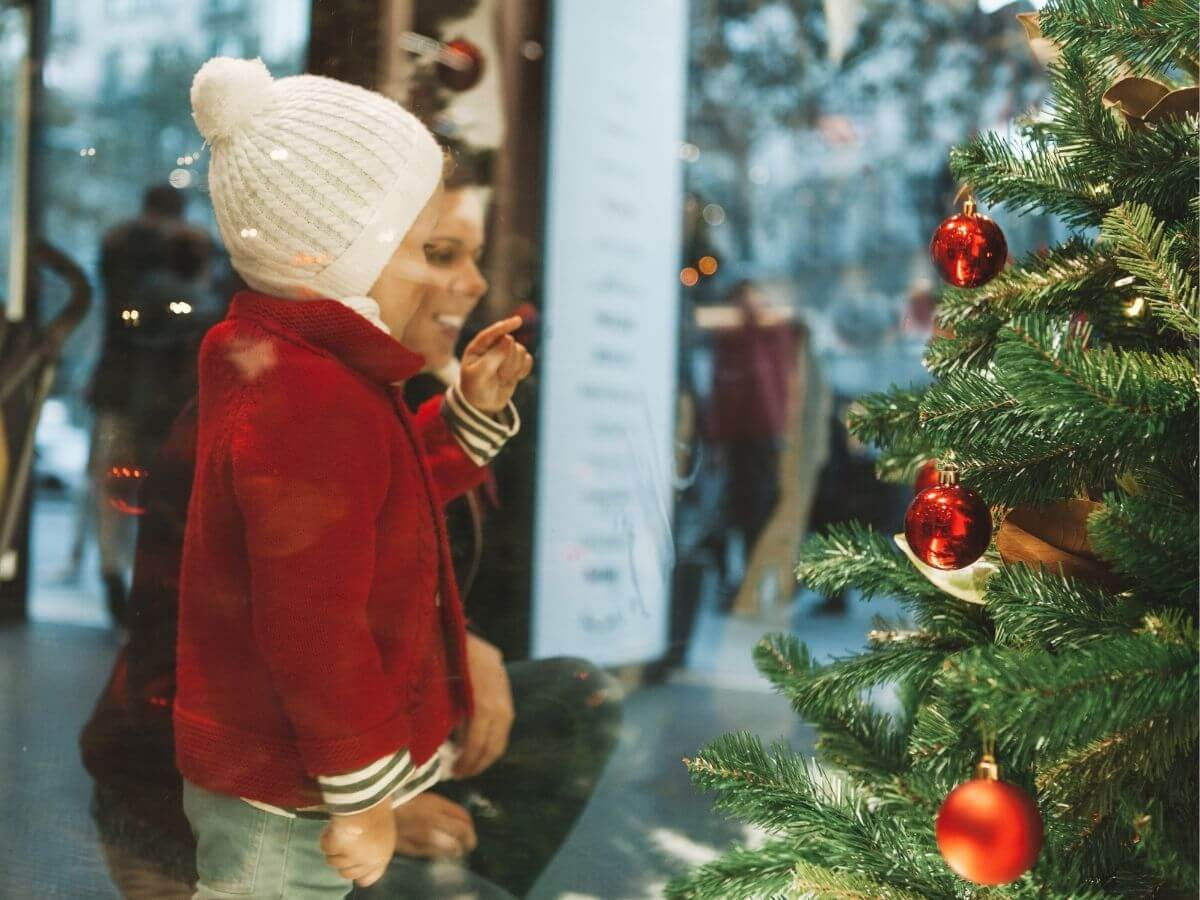 Mother & Child looking through shop window at Christmas tree