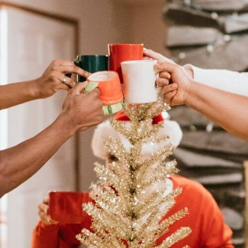 4 hands cheering mugs together in front of small Christmas tree with Santa figure in background behind