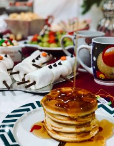 Syrup being poured onto Christmas pancakes at an Elf on the Shelf Breakfast