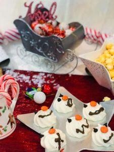 Meringue Snowman faces on table of festive treats