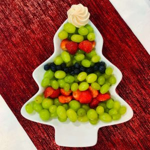 Grapes, strawberries and blueberries in a Christmas tree shape with a meringue star