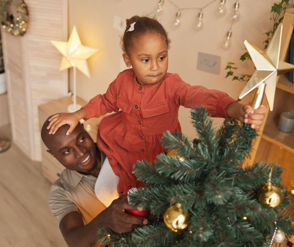 Father holding up daughter to add Star To The Top of the Christmas Tree