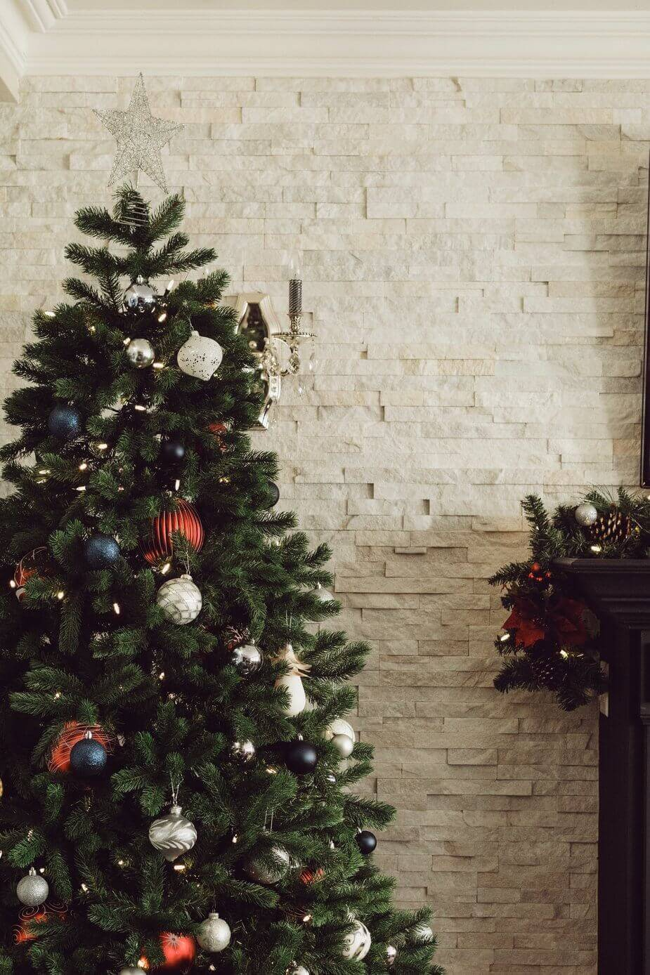 Professionally Decorated Christmas Tree in Red, White & Blue understated baubles with cream brick background