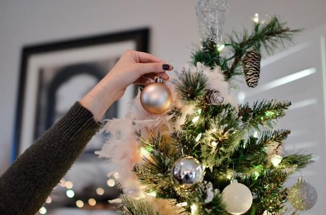 Decorate Christmas Tree Like a Pro - adding matt gold bauble to elegant tree
