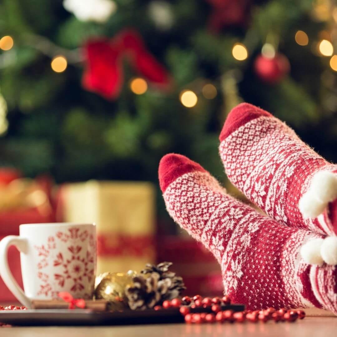Christmas socks up on table with cup of tea and Christmas tree behind