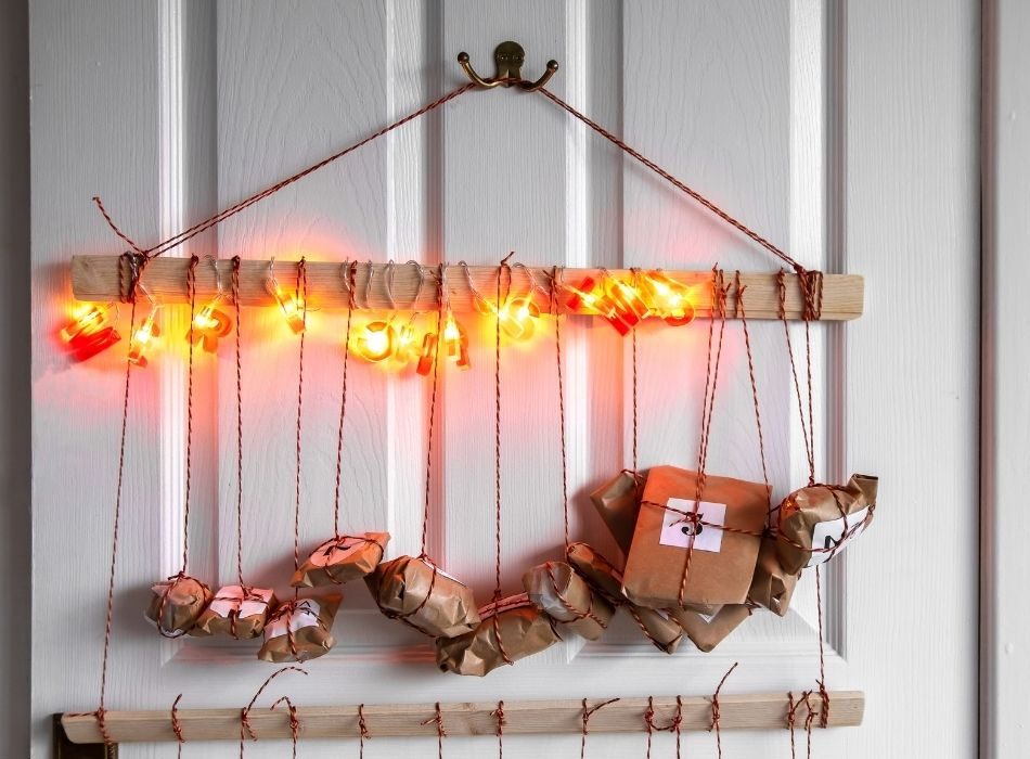 Hanging Homemade Advent Calendar Idea -Small presents hanging with twine from wood strip