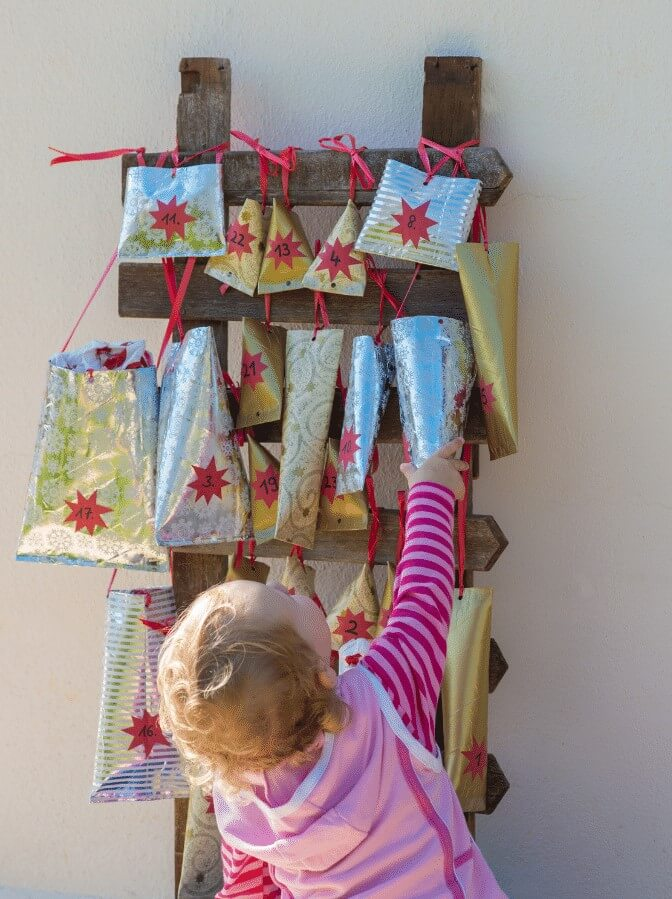 Toddler Reaching For a Parcel On A Homemade Advent Calendar